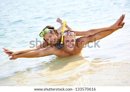 Happy guy and girl in scuba masks playing in water