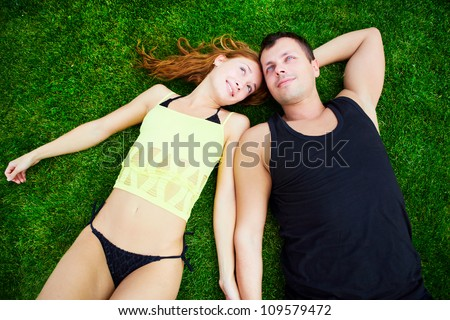 Happy guy and the girl lie on a grass - stock photo