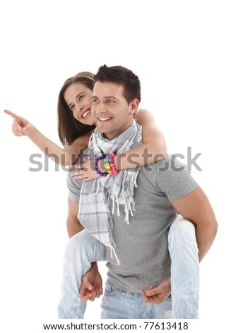Happy guy carrying girlfriend on back, girl pointing, laughing, wearing casual summer clothes, isolated on white.?