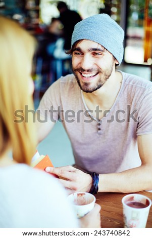 Happy guy looking at his girlfriend while talking to her