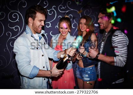 Happy guy opening bottle of champagne at party - stock photo