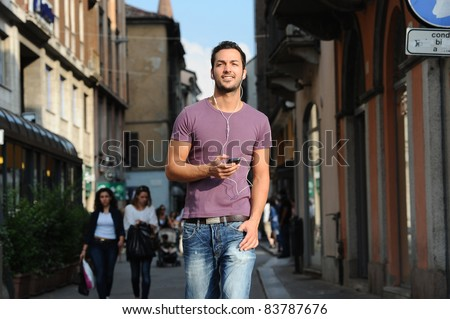 happy guy while talking on the phone to the streets of his city - stock photo