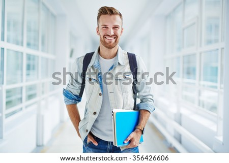 Happy guy with book and touchpad looking at camera - stock photo