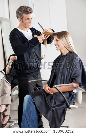 Happy hairstylist cutting female customer's hair with client in background in parlor