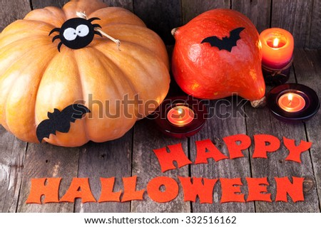 Happy halloween background. Pumpkins, candles, handmade letters Happy Halloween and decorations on old wooden background
