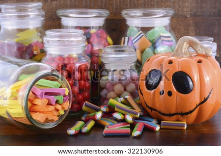 Happy Halloween Candy in Glass Apothecary Jars with orange pumpkin Jack O Lantern closeup on dark wood table.  - stock photo
