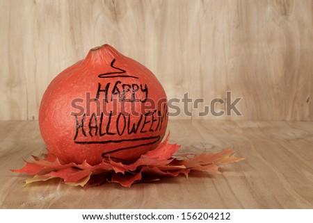 Happy Halloween inscription on the pumpkin, on wood surface - stock photo