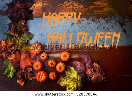 Happy Halloween on wooden board with pumpkins and leaves