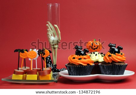 Happy Halloween party food with skeleton hand glass, with cupcakes and cocktail snacks on red background. - stock photo