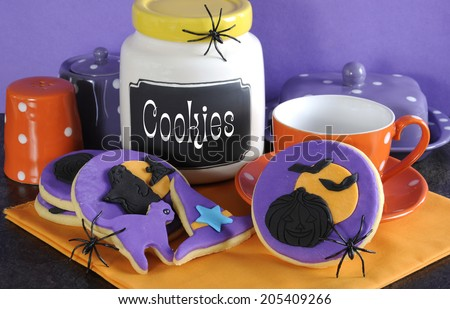 Happy Halloween party trick or treat purple and orange cookies with spiders and cookie jar. - stock photo