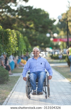 Happy handicapped person on a wheelchair at the park - stock photo