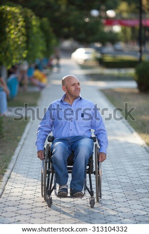 Happy handicapped person on a wheelchair at the park