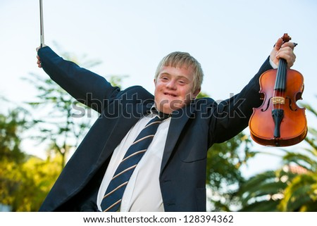 Happy handicapped violinist raising arms outdoors. - stock photo