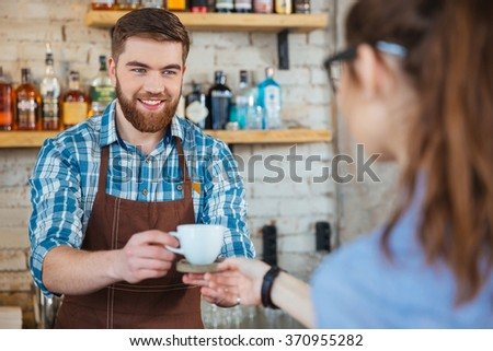 Happy handsome barista in brown apron giving cup of coffee to young woman in coffee shop - stock photo