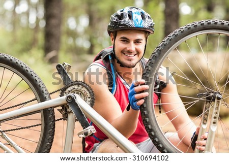 Happy handsome biker repairing bike and looking at camera in the nature