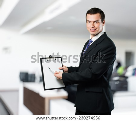Happy handsome business man car dealer pointing a pen on a white-board with copy space on office background - stock photo