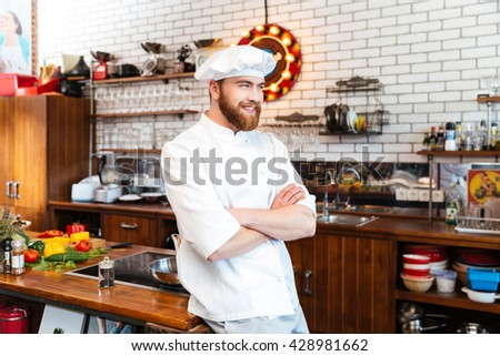 Happy handsome chef cook standing on the kitchen and smiling - stock photo