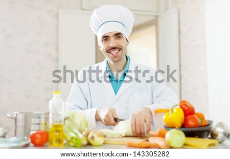 Happy handsome cook does veggie lunch  from vegetables at kitchen - stock photo