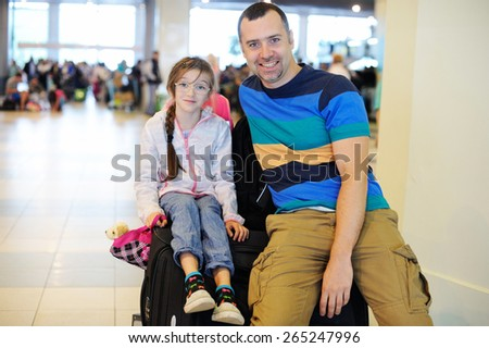 Happy handsome  father and daughter with the luggage at airport