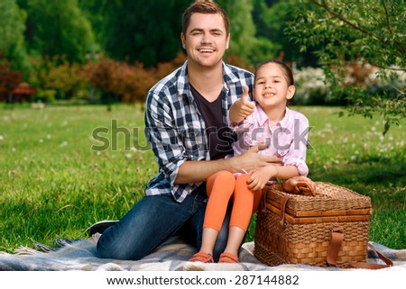 Happy handsome father sitting on a plaid on a green grass holding his small pretty daughter on his knees and hugging her, both smiling, wicker basket for picnic near