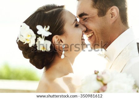 Happy handsome groom and beautifyl bride hugging on balcony at sunset closeup - stock photo