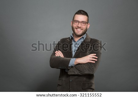 Happy handsome hipster man smiling for the camera. Man in glasses showing his teeth with folded arms in photo studio. - stock photo