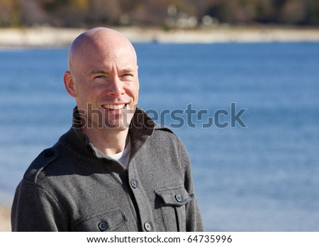 Happy handsome man at beach smiling portrait - stock photo