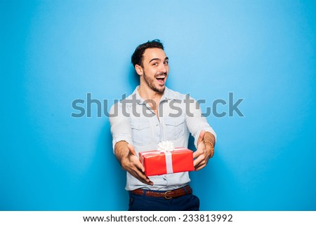 happy handsome man giving a christmas gift, on blue background - stock photo