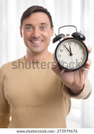 happy handsome man holding alarm clock close up - stock photo