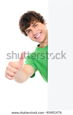 Happy handsome man showing thumbs up look out from white blank banner - stock photo
