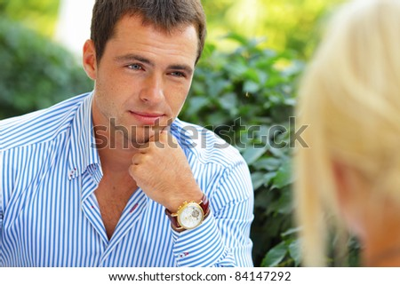 Happy handsome man sitting on the date in front of his girlfriend - stock photo