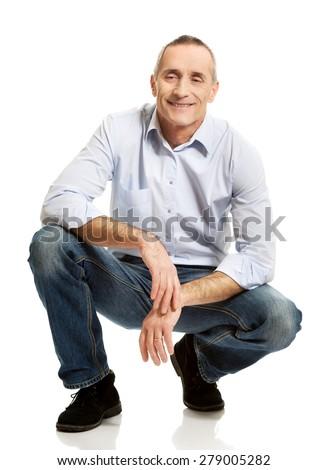 Happy handsome mature man squatting. - stock photo