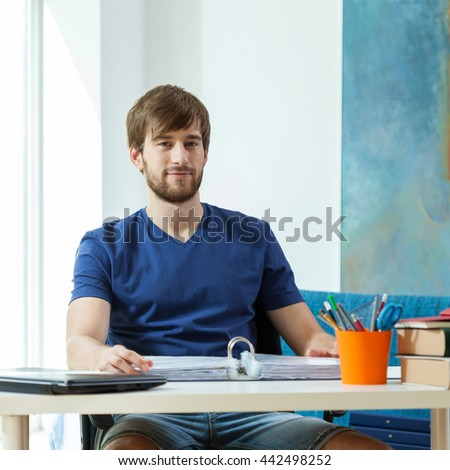 Happy handsome student sitting at his his desk - stock photo