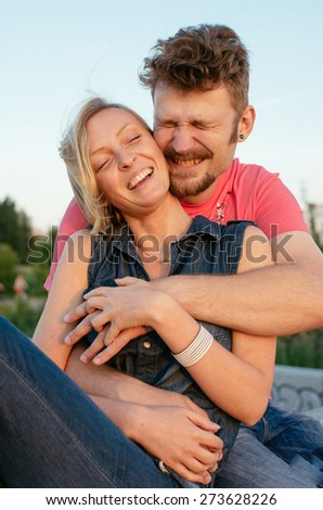 happy handsome young couple embracing and laughing