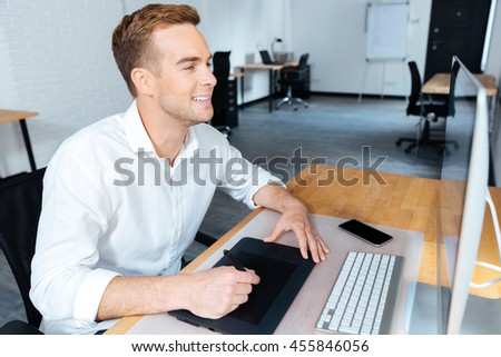 Happy handsome young male designer using computer and graphic tablet in office - stock photo