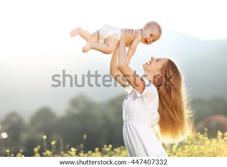 happy harmonious family outdoors. mother throws baby up, laughing and playing in the summer on the nature - stock photo