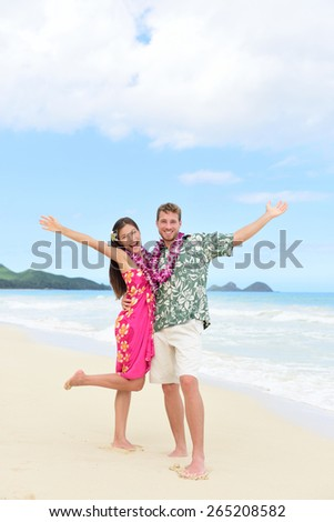 Happy Hawaii vacation couple having fun on beach holidays in Hawaii standing on perfect white sand with arms up in joy and happiness. People ready for summer vacations showing freedom and success. - stock photo
