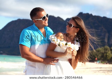 Happy Hawaii vacation couple relaxing together enjoying their holidays in perfect getaway in sunny tropical destination. Couple in love, summer luxury vacation in Hawaii. Living, loving and laughing - stock photo