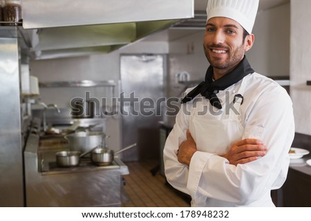 Happy head chef smiling at camera with arms crossed in a commercial kitchen - stock photo