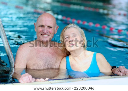 Happy healthy active senior couple having fun swimming together in the pool - stock photo