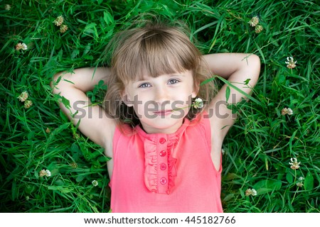 Happy healthy Caucasian kid with heart-shaped hair lying on the grass field background: Little girl child in beautiful green environment: Peaceful mind girl in clean natural greenery surroundings - stock photo