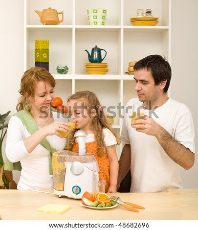 Happy healthy family drinking freshly squeezed orange juice - stock photo
