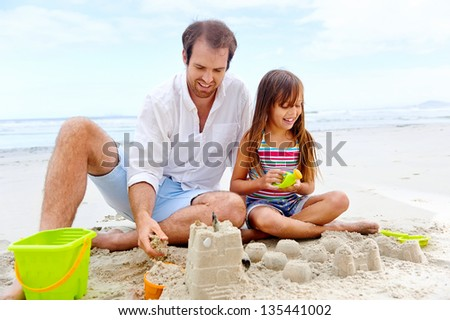 happy healthy family father and daughter building sand castle on the beach smiling and carefree - stock photo