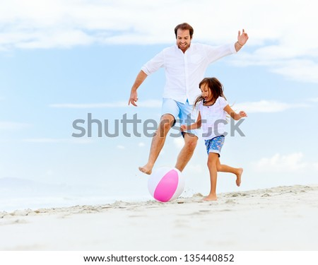 happy healthy family father and daughter running on the beach with ball having fun together - stock photo