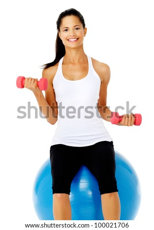 Happy healthy fit asian woman sitting on a pilates gym ball while lifting dumbbells, isolated on white - stock photo