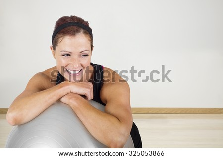 Happy healthy fitness woman resting on a exercise ball. Candid portrait of a smiling woman resting after exercising at an indoor gym - stock photo