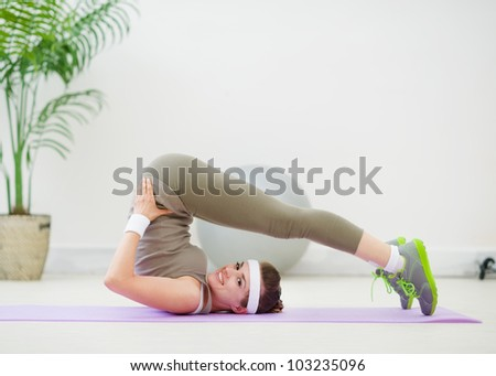 Happy healthy girl doing stretching exercises on floor
