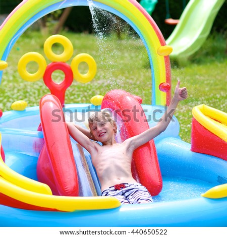 Happy healthy kid having fun in inflatable play centre. Child enjoying summer holidays playing in the pool at the backyard in the garden. Schoolboy relaxing on hot sunny day. - stock photo