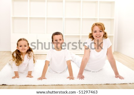 Happy healthy kids and their mother doing gymnastic exercises - healthy life concept - stock photo
