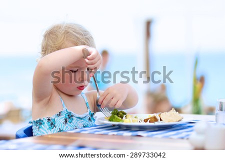 Happy healthy little child, cute blonde toddler girl, enjoying summer vacations eating potato, broccoli and other meal sitting in high chair at beach restaurant with sea view in tropical resort - stock photo